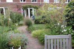 Tuin Judith en Jeroen Rotterdam. Grondplan met slingerpad en heuveltjes waardoor niet meer te zien is dat dit  een paar jaar geleden nog een kale nieuwbouwtuin was. Aangeplant met grassen en insecten en vogels lokkende beplanting. aug 2020